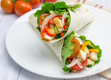 Tortilla wraps with roasted chicken fillet, fresh vegetables and sauce on white plate