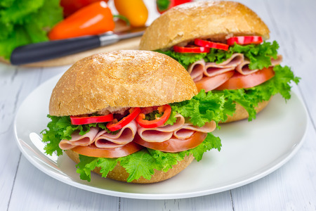 Healthy sandwiches with ham and a wooden board with vegetables on background