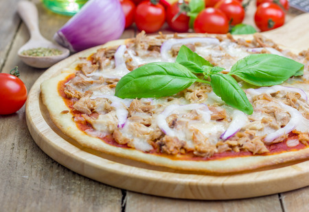 Pizza with tuna fish on a wooden board Stock Photo