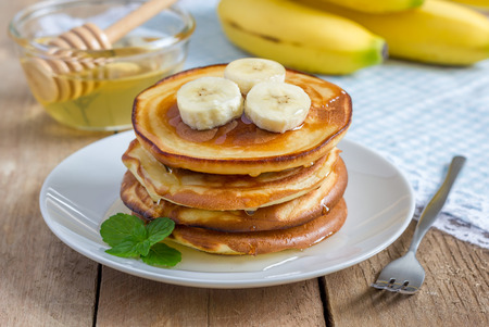 Stack of pancakes with banana and honey