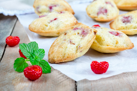 small paper: Madeleines cookie with raspberry on parchment paper, closeup