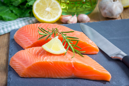 Fresh raw salmon fillet with rosemary and lemon