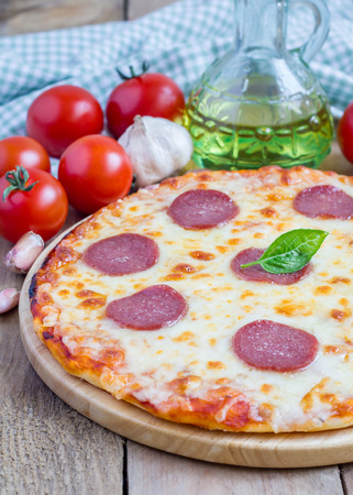unsliced: Homemade pepperoni pizza on a wooden board, ready to eat