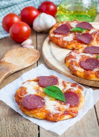 unsliced: Homemade mini pepperoni pizza on a wooden board