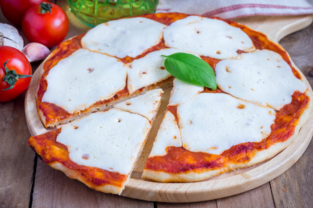 unsliced: Homemade pizza with mozzarella cheese on a wooden board