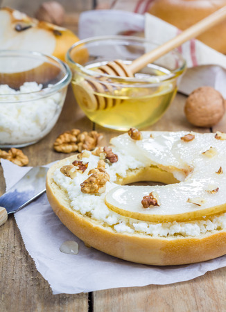 bublik: Fresh bagel with cottage cheese, pear, walnut and honey for breakfast. Concept of healthy eating.
