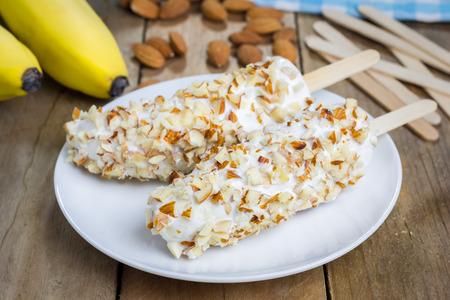 botanas: Plátano congelado cubierto con yogur y almendras Foto de archivo
