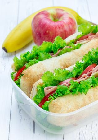 ciabatta: Lunch box with ciabatta bread sandwiches, apple and banana