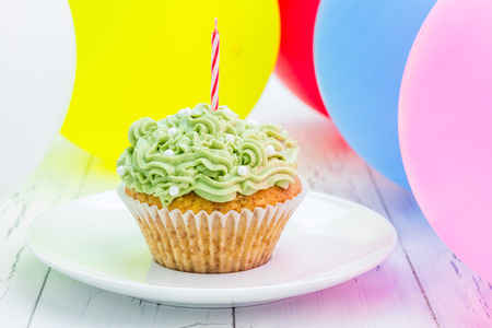 1st birthday: Homemade tasty birthday cupcake with candle, colorful balloons on background Stock Photo