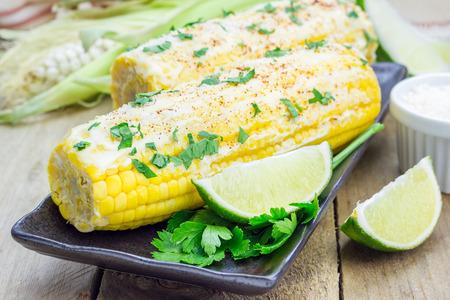 Mexicaanse maïs met boter, mayonaise, parmezaanse kaas, chili, koriander en kalk Stockfoto