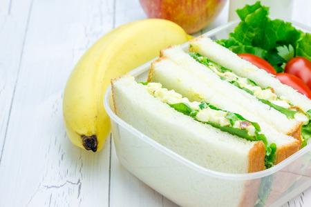 bocadillo: Rectángulo de almuerzo con ensalada de huevo sándwiches, manzana, plátano y leche