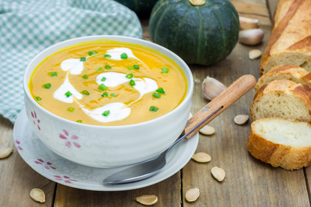 pumpkin soup: Pumpkin soup with sour cream on a wooden table Stock Photo