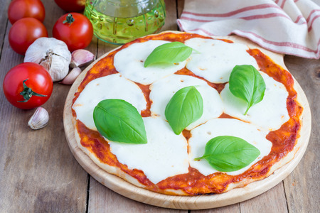 Homemade margherita pizza on a wooden board