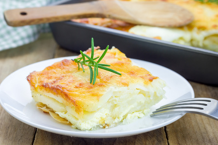 oven potatoes: Potato gratin on a white plate