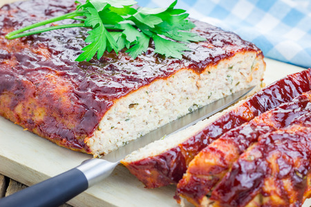 meatloaf: Homemade meatloaf with ketchup and parsley on a wooden board