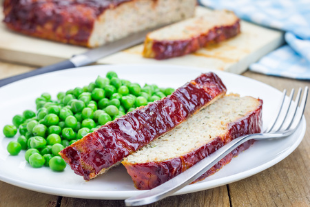 meatloaf: Homemade meatloaf garnished with green peas on a white plate Stock Photo