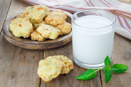 milk and cookies: Fresh baked cheese cookies with basil, closeup Stock Photo