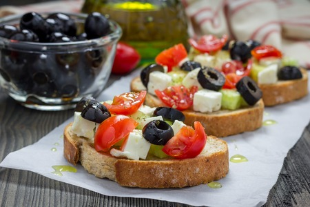 collation: Greek style crostini with feta cheese, tomatoes, cucumber, olives and herbs