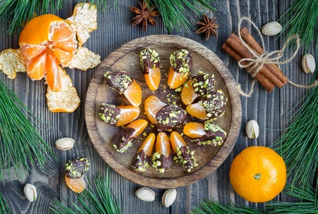 orange fruit: Mandarins covered with chocolate and pistachio, top view Stock Photo