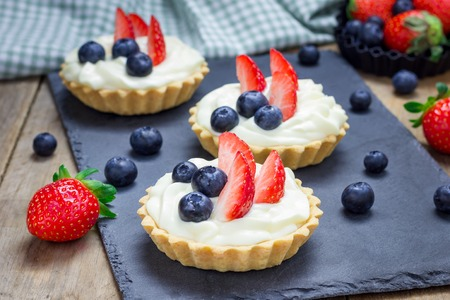 shortbread: Homemade shortbread tartlets with custard cream, strawberry and blueberry