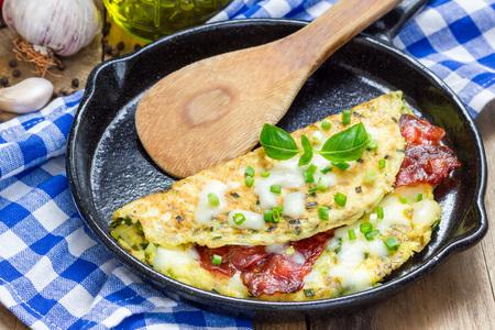 Speck gefüllte Omelett auf einer Eisengusspfanne Standard-Bild