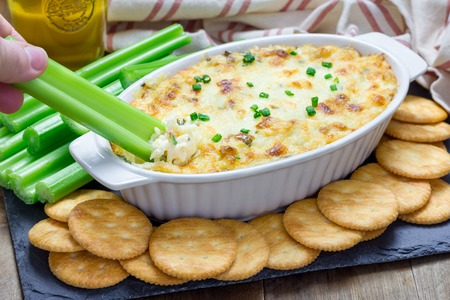 Baked crab dip, served with celery sticks and crackers