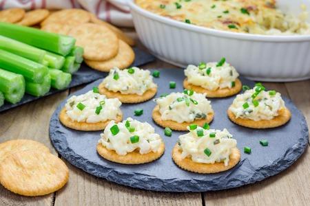 Gebakken krab dipsaus, geserveerd met selderij sticks en crackers
