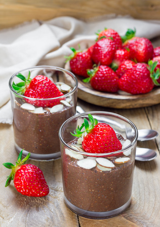 Chocolate chia seed pudding garnished with almond slices and strawberry