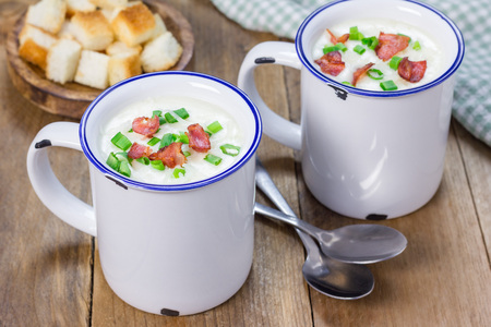 garnished: Creamy potato soup garnished with bacon and green onion, served in mug Stock Photo