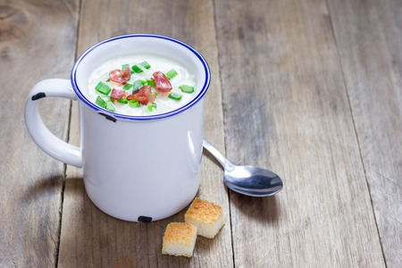 garnished: Creamy potato soup garnished with bacon and green onion, served in mug, copy space Stock Photo