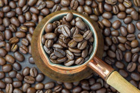 cezve: Fragrant coffee beans in copper cezve, top view, close up Stock Photo
