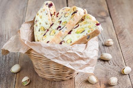 Biscotti con arándano rojo y pistacho en cesta de la vid Foto de archivo - 56440576