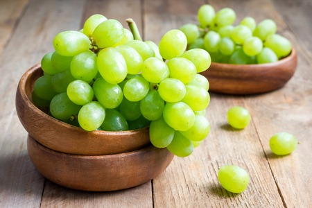 Bunch of green ripe grapes in a wooden bowl, on rustic wood background