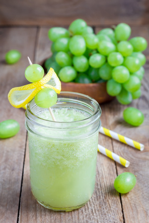 Healthy smoothie with green grape, lemon and honey in glass jar