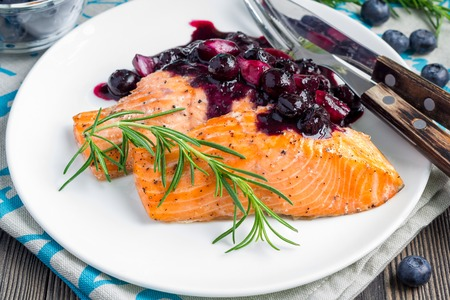 rosmarin: Baked salmon fillet with blueberry and rosmarin sauce on white plate, horizontal Stock Photo