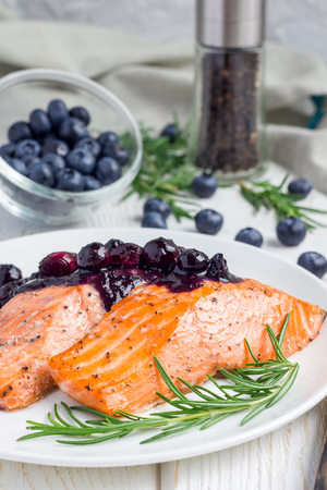 rosmarin: Baked salmon fillet with blueberry and rosmarin sauce on white plate, vertical Stock Photo
