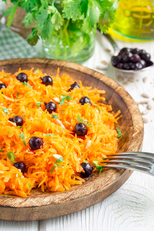 Healthy vegetarian salad with carrot, black currant, cilantro, sunflower and sesame seeds, on white wooden table, vertical Stock Photo