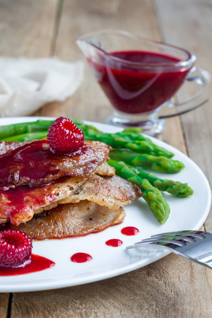 Pork cutlets with raspberry sauce and asparagus on white plate, vertical Stock Photo
