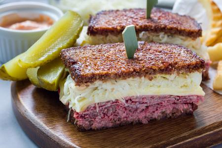 Classic reuben sandwich met corned beef, Zwitserse kaas, zuurkool en Thousand Island dressing op Fries roggebrood, geserveerd met een augurk speer en chips, horizontaal
