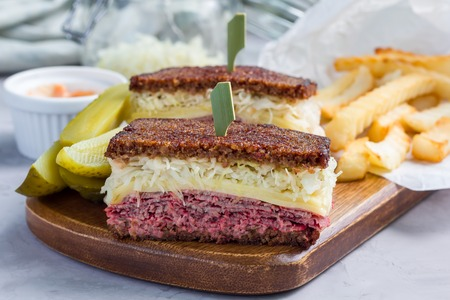 Classic reuben sandwich with corned beef, swiss cheese, sauerkraut and thousand island dressing on pumpernickel bread, served with dill pickle spear and potato chips, horizontal Stock Photo