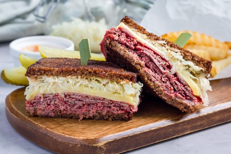 Classic reuben sandwich with corned beef, swiss cheese, sauerkraut and thousand island dressing on pumpernickel bread, served with dill pickle spear and potato chips, horizontal Banco de Imagens