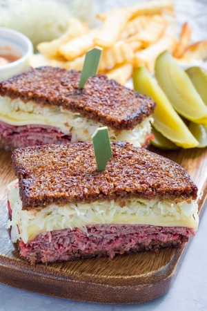 reuben: Classic reuben sandwich with corned beef, swiss cheese, sauerkraut and thousand island dressing on pumpernickel bread, served with dill pickle spear and potato chips, vertical Stock Photo