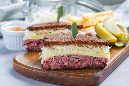 reuben: Classic reuben sandwich with corned beef, swiss cheese, sauerkraut and thousand island dressing on pumpernickel bread, served with dill pickle spear and potato chips, horizontal Stock Photo