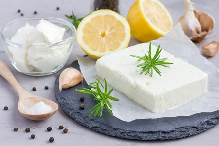 Ingredients for feta, cream cheese, rosemary, lemon and garlic dip on slate board