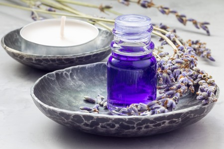 flowers horizontal: Lavender oil in a glass bottle on background with lavender flowers. Horizontal close-up