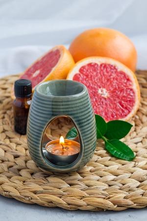Aroma lamp met grapefruit etherische olie op geweven mat, grapefruits op de achtergrond, verticaal