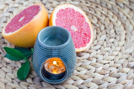 Aroma lamp with grapefruit essential oil on woven mat, grapefruits on background, horizontal Stock Photo
