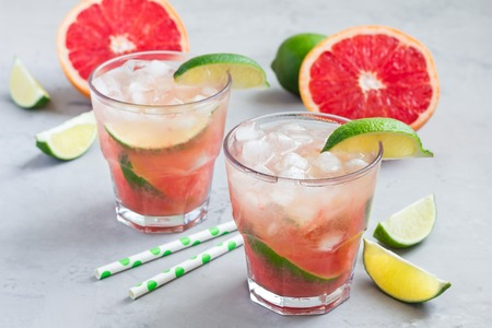 Cold pink cocktail with fresh grapefruit, lime and ice cubes on concrete background, paloma Imagens
