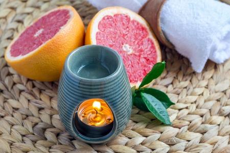 Aroma lamp met grapefruit etherische olie op geweven mat, grapefruits op de achtergrond, horizontale Stockfoto