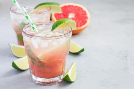 Koud roze cocktail met verse grapefruit, kalk en ijsblokjes op concrete achtergrond, paloma, exemplaarruimte Stockfoto